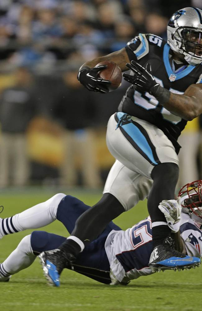 Carolina Panthers' Mike Tolbert, top, is tackled by New England Patriots' Devin McCourty, bottom, during the second half of an NFL football game in Charlotte, N.C., Monday, Nov. 18, 2013