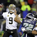 In this Dec. 2, 2013, file photo, New Orleans Saints quarterback Drew Brees (9) passes under pressure from Seattle Seahawks defensive end Michael Bennett (72) during an NFL football game in Seattle. NFL free agency begins Tuesday, March 11, 2014, with eac