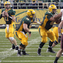 In this Sept. 20, 2014 file photo North Dakota State quarterback Carson Wentz, left, gets ready to throw against Montana during an NCAA college football game Saturday in Fargo, North Dakota. Wentz is showing why North Dakota State football coaches groome