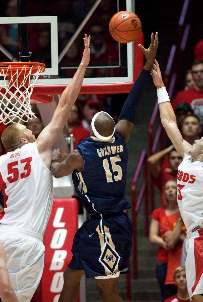 Charleston Southern's Paul Gombwer shoots over the defense of New Mexico's Alex Kirk, left, and Hugh Greenwood and in the second half of an NCAA basketball game, Sunday, Nov. 17, 2013 in Albuquerque, N.M. New Mexico won 109-93