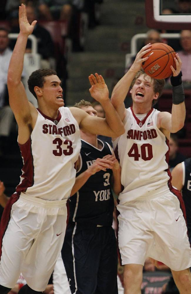 Stanford's John Gage (40) rebounds next to teammate Dwight Powell (33) during the second half of an NCAA college basketball game against Brigham Young, Monday, Nov. 11, 2013, in Stanford, Calif. Brigham Young's Tyler Haws is behind