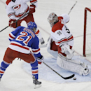 New York Rangers' Derek Stepan (21) shoots the puck past Carolina Hurricanes' Cam Ward (30) during the third period of an NHL hockey game Tuesday, April 8, 2014, in New York. The Rangers won 4-1 The Associated Press