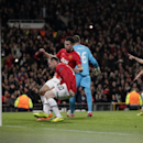 Manchester United's Robin van Persie, second left, Wayne Rooney, left, and Patrice Evra, right, run in to retrieve the ball for the restart after van Persie scored a penalty for his side's first goal during their Champions League last 16 second leg soccer