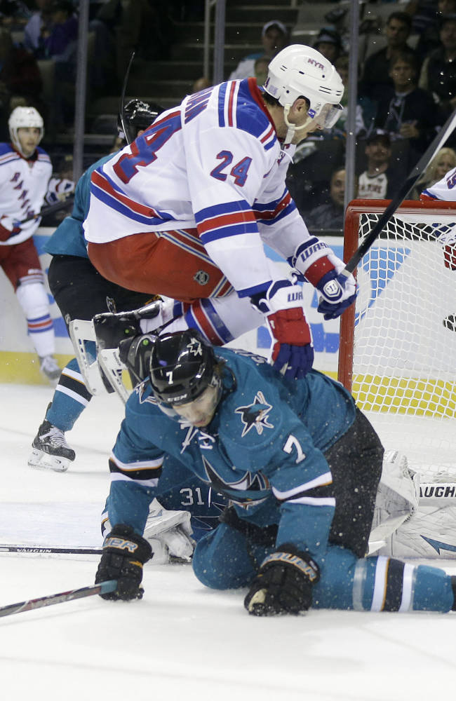 New York Rangers' Ryan Callahan (24) jumps over San Jose Sharks' Brad Stuart (7) during the second period of an NHL hockey game on Tuesday, Oct. 8, 2013, in San Jose, Calif