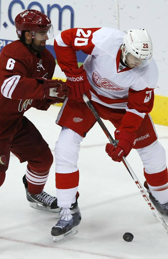 Phoenix Coyotes defenseman David Schlemko (6) tries to slow Detroit Red Wings left wing Drew Miller (20) in the second period of an NHL hockey game Saturday, Oct. 19, 2013, in Glendale, Ariz