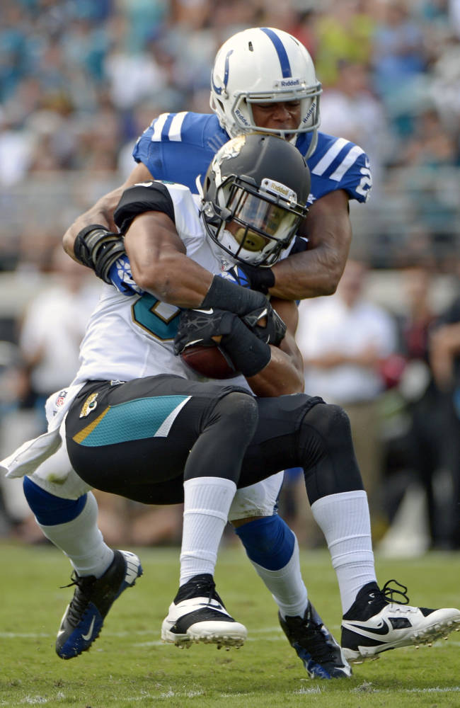Jacksonville Jaguars wide receiver Cecil Shorts, front, is tackled by Indianapolis Colts cornerback Darius Butler after a reception during the first half of an NFL football game in Jacksonville, Fla., Sunday, Sept. 29, 2013