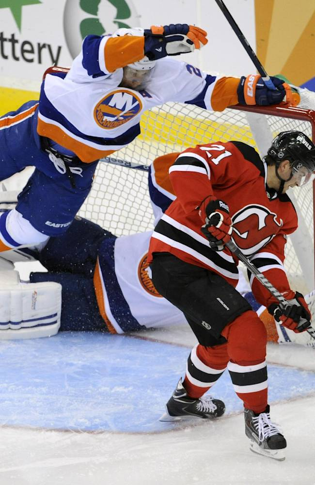 New York Islanders' Kyle Okposo, left, flies over Islanders goaltender Kevin Poulin as New Jersey Devils' Andrei Loktionov, right, handles the puck during the third period of a preseason NHL hockey game, Thursday, Sept. 19, 2013, in Newark, N.J. The Islanders defeated the Devils 5-3