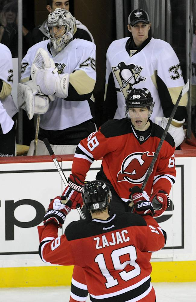 New Jersey Devils' Jaromir Jagr (68), of Czech Republic, celebrates his unassisted empty-net goal with Travis Zajac (19) as Pittsburgh Penguins goaltenders Marc-Andre Fleury and Jeff Zatkoff (37) stand by during the third period of an NHL hockey game Saturday, Nov. 16, 2013, in Newark, N.J. The Devils won 4-1