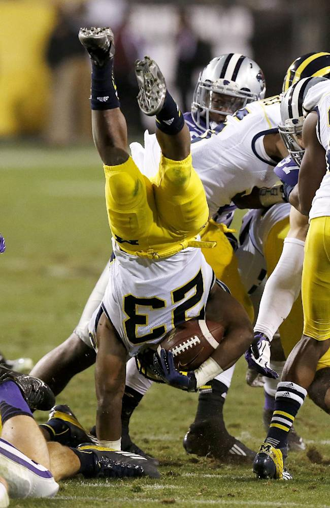 Michigan's Dennis Norfleet (23) is upended by Kansas State defenders on a kickoff during the second half of the Buffalo Wild Wings Bowl NCAA college football game, Saturday, Dec. 28, 2013, in Tempe, Ariz. Kansas State defeated Michigan 31-14