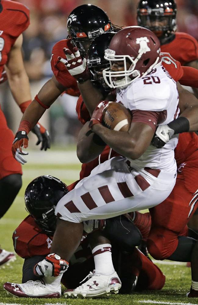 Temple running back Kenneth Harper (20) is stopped after a short gain in the first half of an NCAA college football game against Cincinnati, Friday, Oct. 11, 2013, in Cincinnati