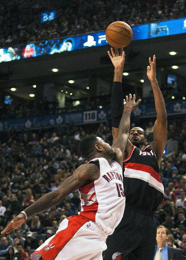 Portland Trail Blazers' LaMarcus Aldridge goes up for a shot against Toronto Raptors' Amir Johnson during an NBA basketball game in Toronto on Sunday, Nov. 17, 2013