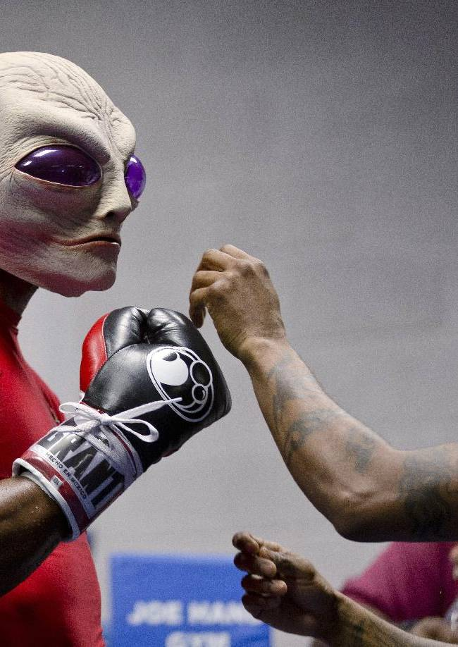 Boxer Bernard Hopkins puts on an alien mask with the help of assistant trainer Danny Davis during a media workout Wednesday, Oct. 16, 2013, in Philadelphia. Hopkins is scheduled to fight Karo Murat at Boardwalk Hall in Atlantic City, N.J., on Oct. 26