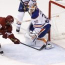 Arizona Coyotes' Martin Erat (10), of the Czech Republic, gets the puck past Edmonton Oilers' Ben Scrivens (30) for a goal during the third period of an NHL hockey game Wednesday, Oct. 15, 2014, in Glendale, Ariz. The Coyotes defeated the Oilers 7-4 The