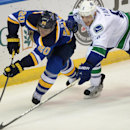 St. Louis Blues' Alexander Steen (20) and Vancouver Canucks' Christopher Tanev (8) reach for the puck during the third period of an NHL hockey game, Thursday, Oct. 23, 2014, in St. Louis. The Canucks won 4-1 The Associated Press