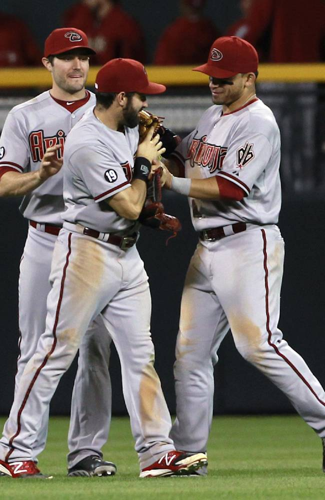 Arizona Diamondbacks outfielders Adam Eaton, front left, and Gerardo Parra, front right, celebrate with A.J. Pollock, back, after the Diamondbacks' 7-2 victory over the Colorado Rockies in a baseball game in Denver on Saturday, Sept. 21, 2013