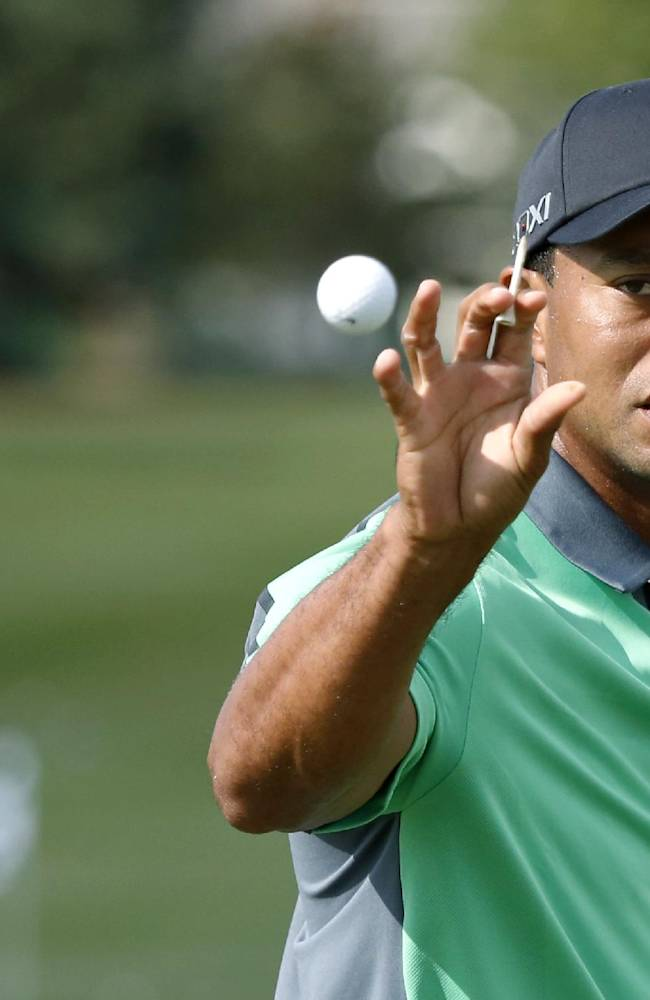 Tiger Woods catches a ball on the driving range from his caddie during the first round of the BMW Championship golf tournament at Conway Farms Golf Club in Lake Forest. Ill., Thursday, Sept. 12, 2013