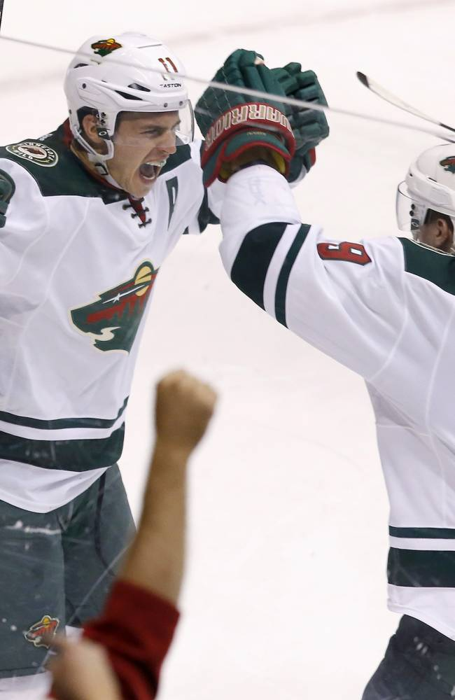 Minnesota Wild's Zach Parise (11) celebrates his empty-net goal against the Phoenix Coyotes with teammate Mikko Koivu (9), of Finland, during the third period of an NHL hockey game, Saturday, March 29, 2014, in Glendale, Ariz. The Wild defeated the Coyotes 3-1