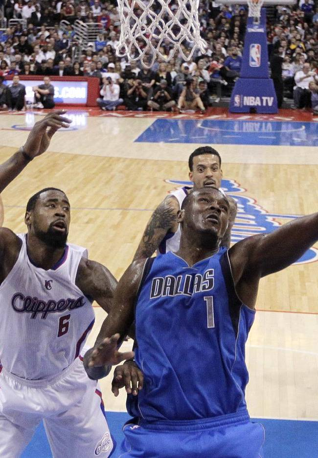 Dallas Mavericks' Samuel Dalembert, right, of Haiti, puts up a shot as Los Angeles Clippers' DeAndre Jordan watches during the second half of an NBA basketball game on Thursday, April 3, 2014, in Los Angeles. The Mavericks won 113-107