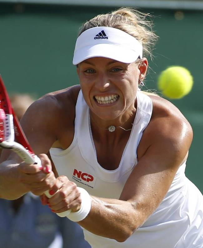 Angelique Kerber of Germany plays a return to Urszula Radwanska of Poland during their first round match at the All England Lawn Tennis Championships in Wimbledon, London, Tuesday, June 24, 2014
