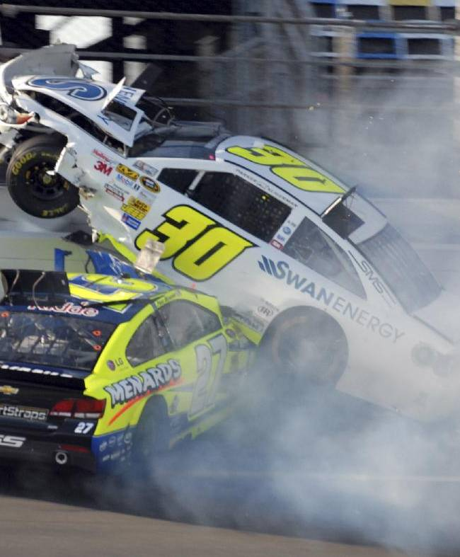 The car driven by Parker Kligerman (30) goes over that driven by Paul Menard (27) during practice for Sunday's NASCAR Daytona 500 auto race at Daytona International Speedway in Daytona Beach, Fla., Wednesday, Feb. 19, 2014