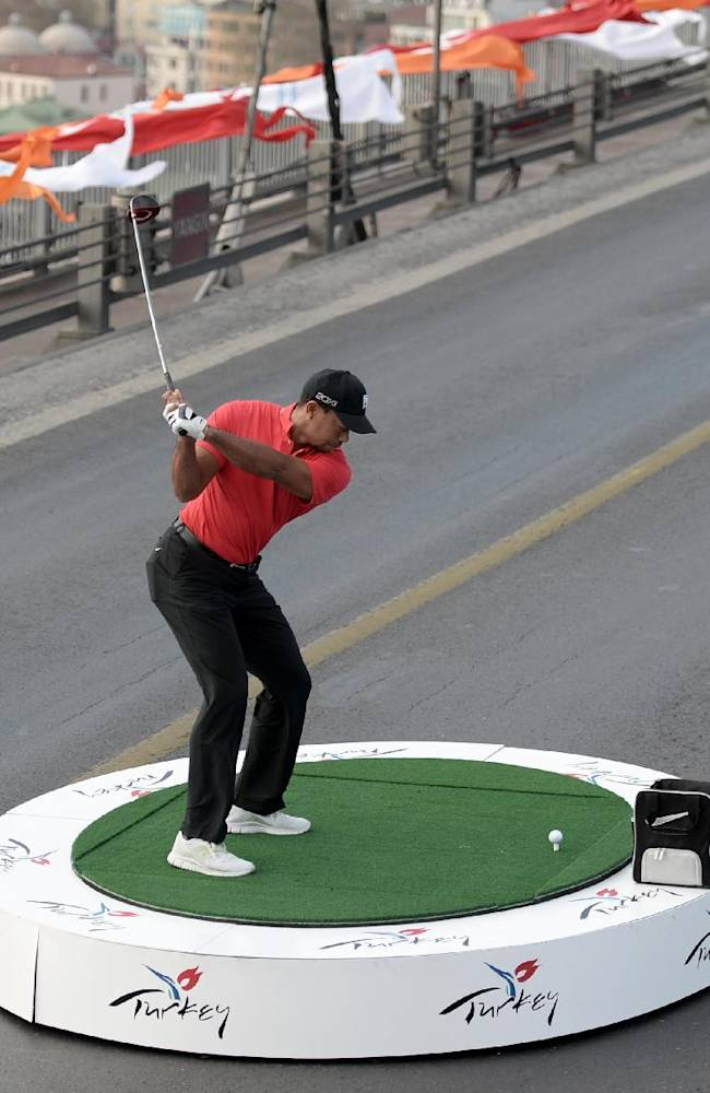 Woods hits golf balls from Europe to Asia