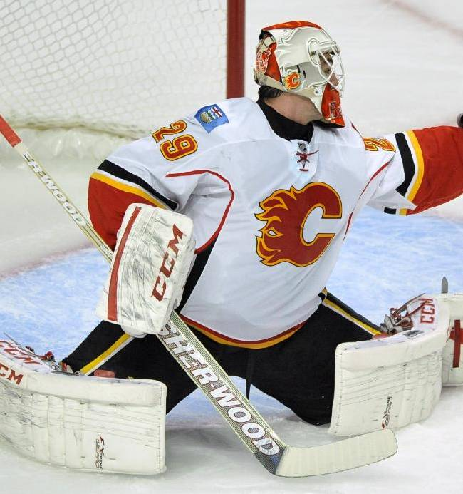 Calgary Flames goalie Reto Berra of Switzerland, makes a save during the first period of an NHL hockey game against the Chicago Blackhawks in Chicago, Sunday, Nov. 3, 2013