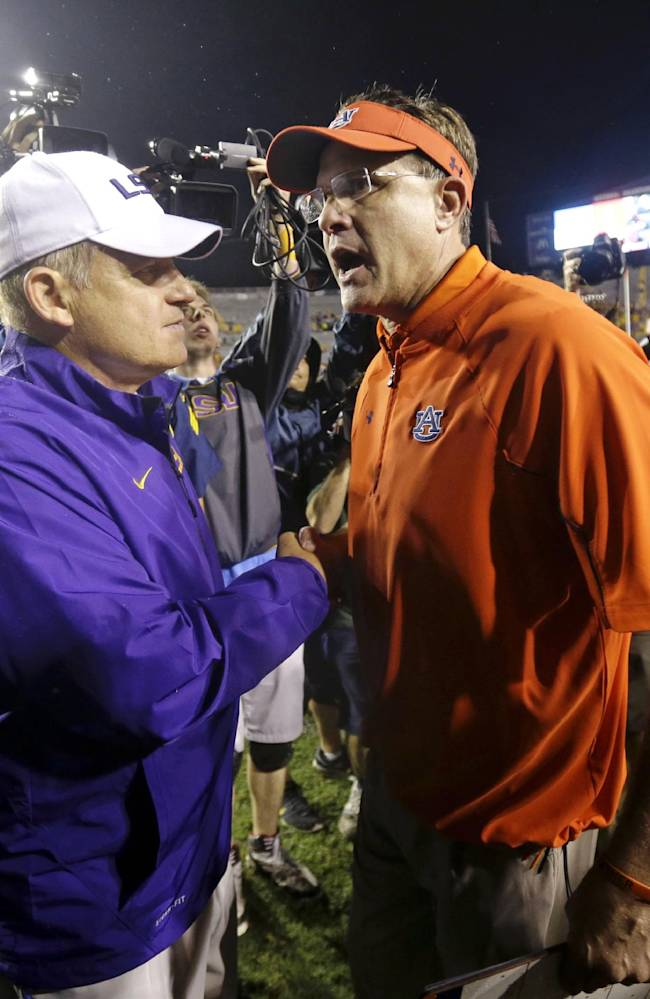In this Sept. 21, 2013 file photo, LSU coach Les Miles, left greets Auburn coach Gus Malzhan after an NCAA college football game in Baton Rouge, La. LSU won 35-21