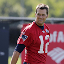 New England Patriots quarterback Tom Brady smiles as he heads to the practice field during an NFL football training camp in Foxborough, Mass., Friday, July 25, 2014 The Associated Press