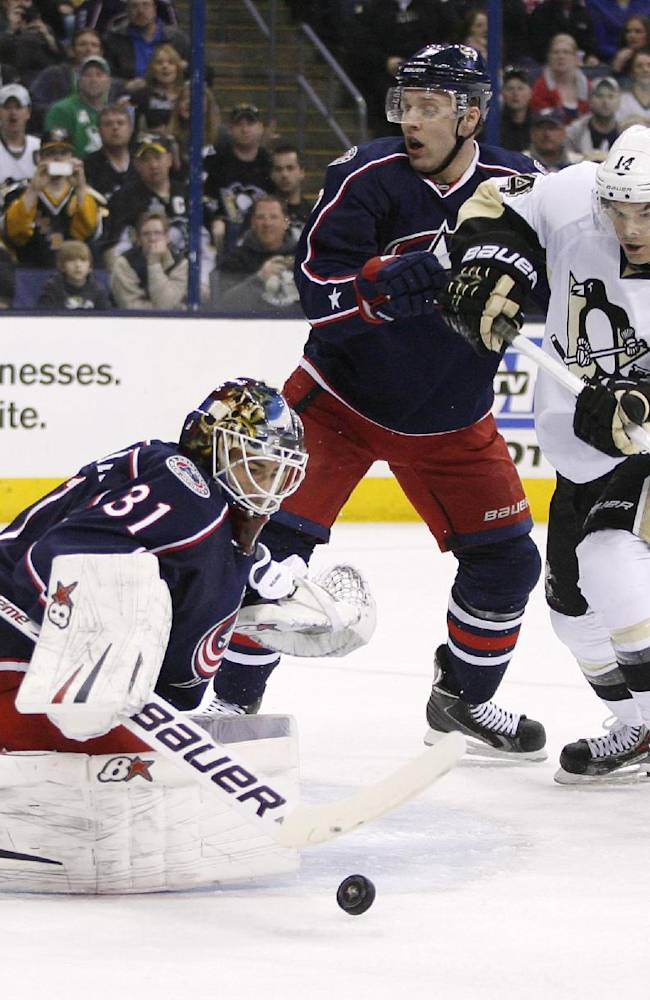Columbus Blue Jackets goalie Curtis McElhinney (31) blocks a shot as Pittsburgh Penguins' Chris Kunitz (14) moves in while being defended by Jack Johnson (7) during the first period of an NHL hockey game, Friday, March 28, 2014, in Columbus, Ohio