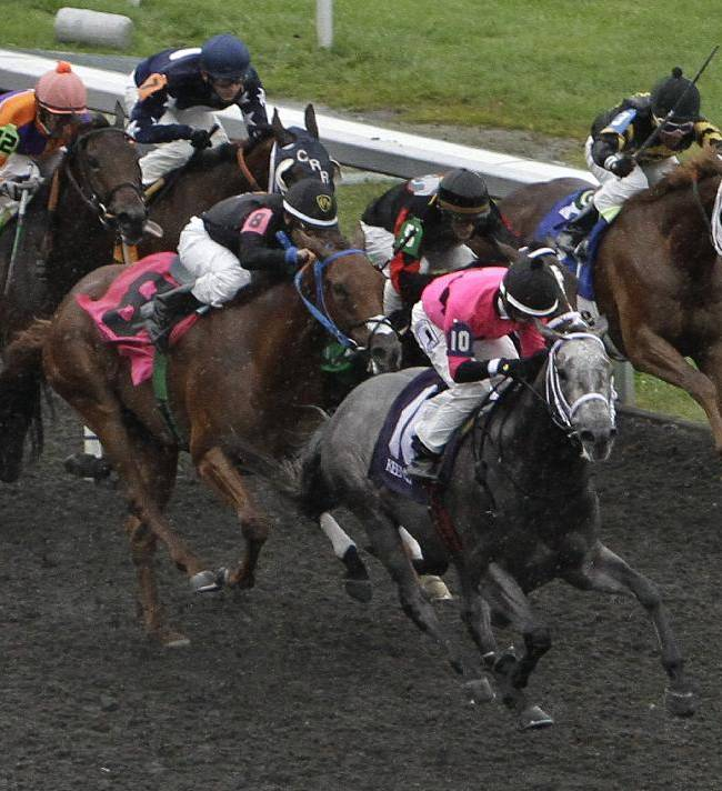 Poker Player, front left, with Channing Hill aboard, passes the competition in the final furlong to win the Bourbon Stakes horse race at Keeneland Race Course in Lexington, Ky., Sunday, Oct. 6,  2013. The race, taken off the turf because of heavy rain, is a
