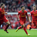 Liverpool's Philippe Coutinho centre, celebrates with team-mates Jon Flanagan right, and Steven Gerrard left, after he scores the third goal of the game for his side during their English Premier League soccer match against Manchester City at Anfield in Li