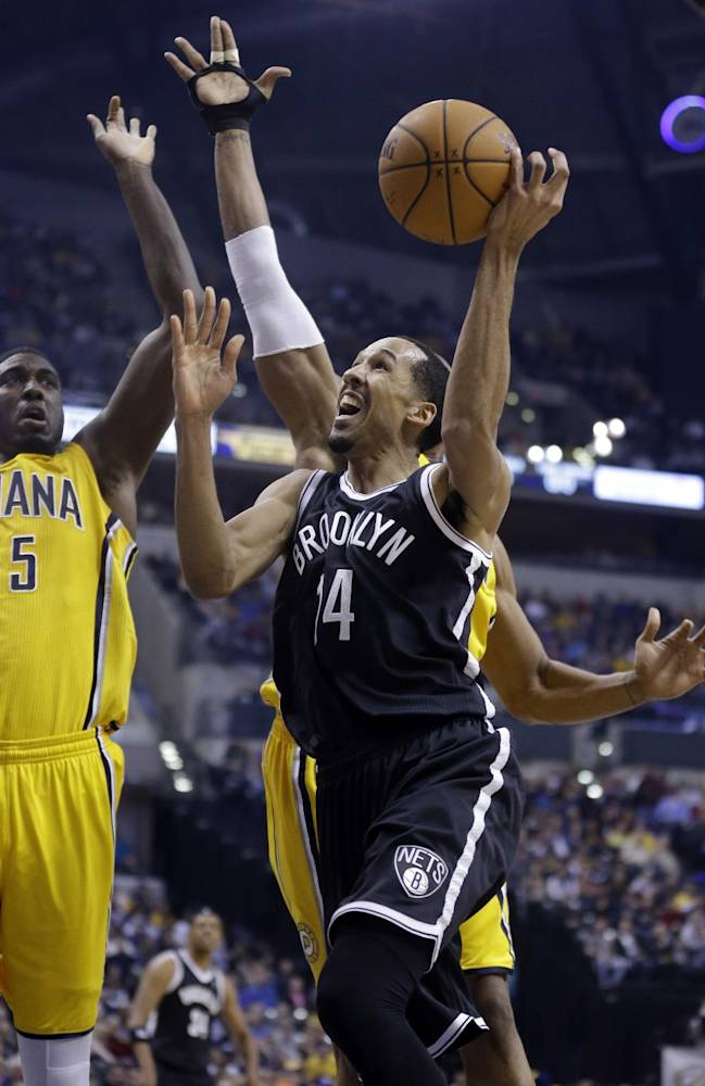 Brooklyn Nets guard Shaun Livingston, right, is fouled as he shoots by Indiana Pacers center Roy Hibbert in the first half of an NBA basketball game in Indianapolis, Saturday, Feb. 1, 2014