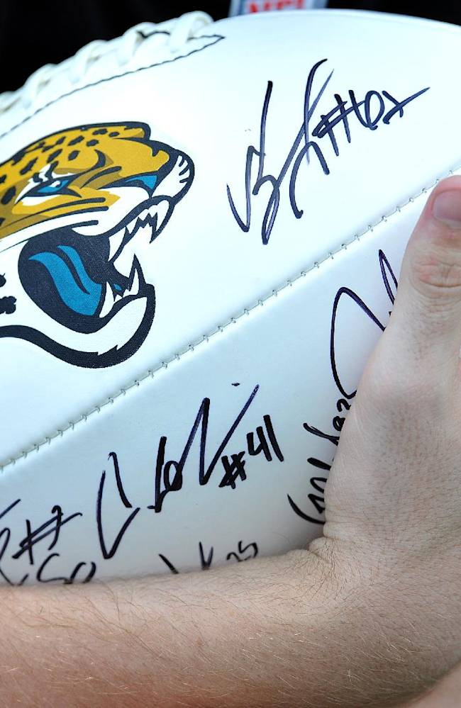 A fan holds a signed football after the Jacksonville Jaguars NFL team's football training camp, on Friday, July 25, 2014, in Jacksonville, Fla