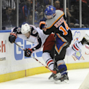 New York Islanders' Thomas Hickey (14) slams Columbus Blue Jackets' Matt Calvert (11) against the boards in the third period of an NHL hockey game on Sunday, March 23, 2014, in Uniondale, N.Y The Associated Press