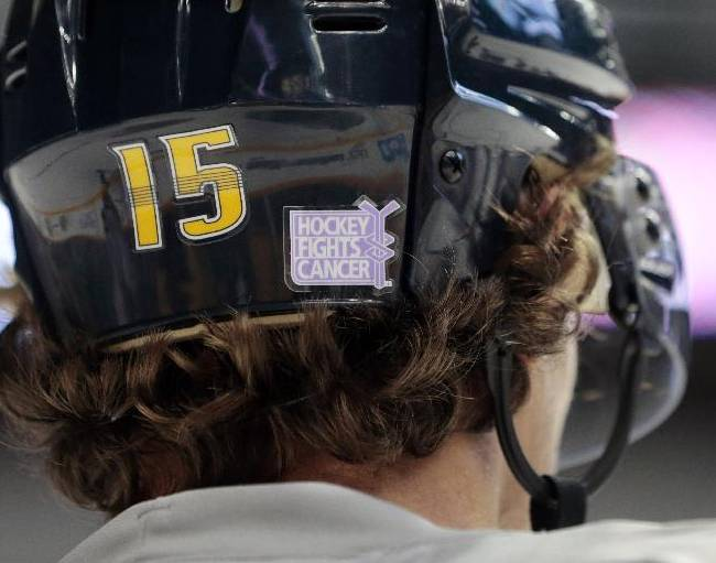 Nashville Predators forward Craig Smith wears a Hockey Fights Cancer logo on his helmet as he warms up before an NHL hockey game against the St. Louis Blues, Saturday, Oct. 26, 2013, in Nashville, Tenn