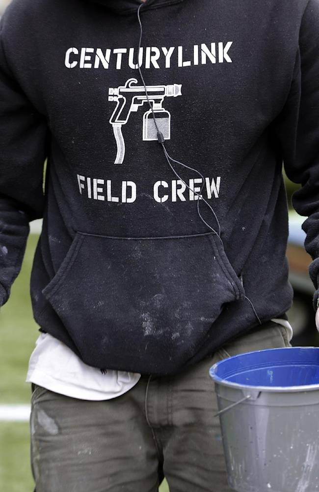 A member of the CenturyLink Field Crew carries a paint bucket as he helps prepare CenturyLink Field for the NFL football NFC championship game in Seattle, Tuesday, Jan. 14, 2014. The game will be played between the Seattle Seahawks and the San Francisco 49ers on Sunday