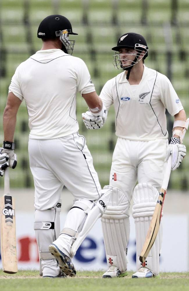 New Zealand's Kane Williamson, right, celebrates with teammate Corey Anderson after scoring half a century on the third day of the second cricket test match against Bangladesh in Dhaka, Bangladesh, Wednesday, Oct. 23, 2013