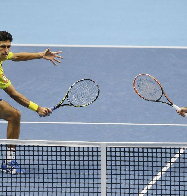 Brazil's Marcelo Melo, left, plays a return to United Sates's Mike Bryan and United States's Bob Bryan, watched by his playing partner Croatia's Ivan Dodig during the doubles final match of the ATP World Tour Finals tennis in London, Sunday, Nov. 16, 2014