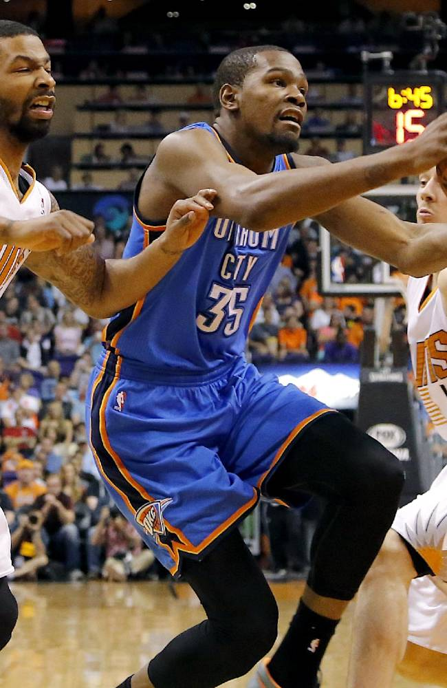 Oklahoma City Thunder forward Kevin Durant (35) drives between Phoenix Suns guard Goran Dragic, right, of Slovenia, and Markieff Morris during the first half of an NBA basketball game on Sunday, April 6, 2014,in Phoenix