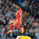 Liverpool's Raheem Sterling jumps over Manchester City goalkeeper Joe Hart during the English Premier League soccer match between Manchester City and Liverpool at the Etihad Stadium, in Manchester, England, Monday, Aug. 25, 2014