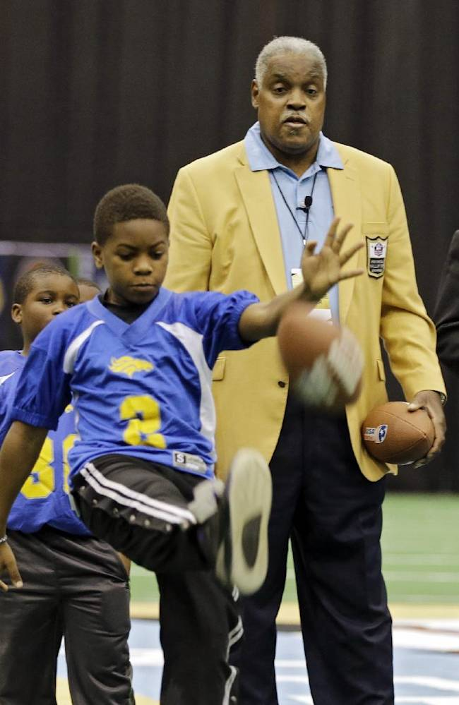 Hall of Fame offensive lineman Art Shell helps with a youth league punt, pass and kick competition at the inaugural Pro Football Hall of Fame Fan Fest Saturday, May 3, 2014, at the International Exposition Center in Cleveland