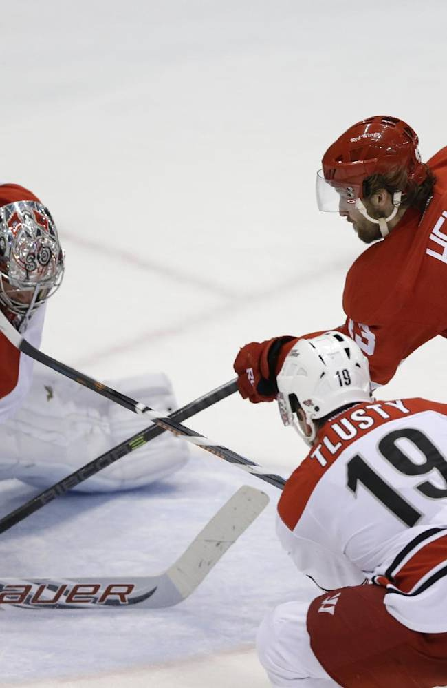 Carolina Hurricanes goalie Cam Ward deflects a shot by Detroit Red Wings center Darren Helm during the third period of an NHL hockey game in Detroit, Friday, April 11, 2014. The Hurricanes defeated the Red Wings 2-1