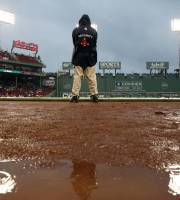 A Fenway Park security guard stands on the field before a baseball game between the Boston Red Sox and the Tampa Bay Rays in Boston, Thursday, July 25, 2013. The game was rained out. (AP Photo/Michael Dwyer)