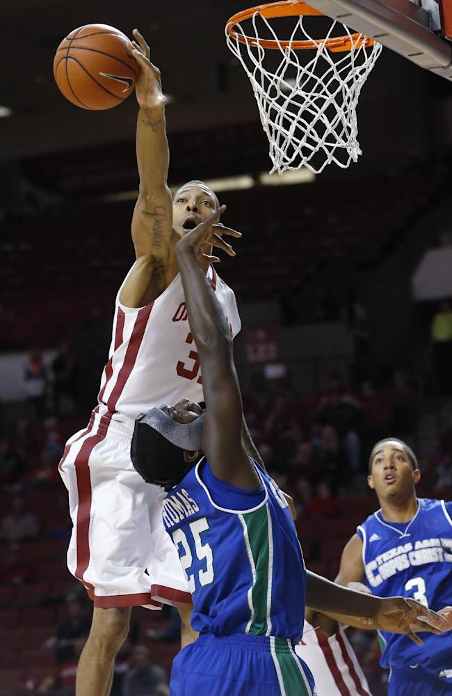 Oklahoma forward D.J. Bennett (31) blocks a shot by Texas A&M Corpus christi forward Rashawn Thomas (25) in the first half of an NCAA college basketball game in Norman, Okla., Thursday, Dec. 5, 2013