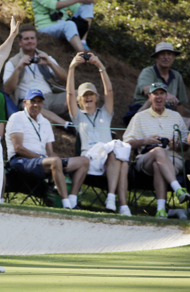 Tennis player Caroline Wozniacki and her fiancee Rory McIlroy, of Northern Ireland, celebrate after Wozniacki putted on the ninth hole during the par three competition at the Masters golf tournament Wednesday, April 9, 2014, in Augusta, Ga. (AP Photo/David J. Phillip)