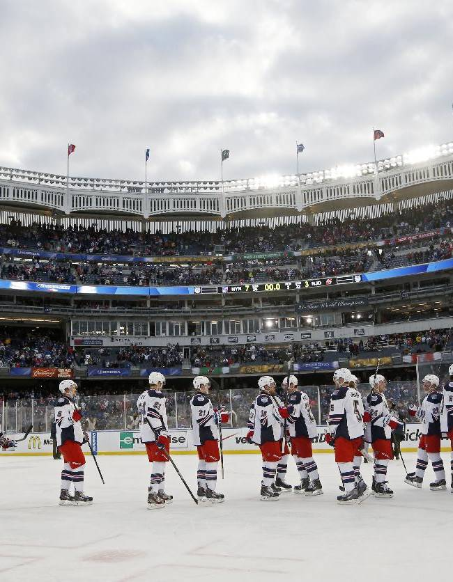 Members of the New York Rangers celebrate their 7-3 victory over the New Jersey Devils after an NHL outdoor hockey game at Yankee Stadium in New York, Sunday, Jan. 26, 2014