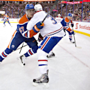 Montreal Canadiens Travis Moen, front right, and Edmonton Oilers David Perron (57) battle in the corner during the first period of an NHL hockey game in Edmonton, Alberta, on Monday, Oct. 27, 2014 The Associated Press