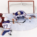 Edmonton Oilers goalie Ben Scrivens (30) makes a save on a shot by Phoenix Coyotes' Shane Doan (19) as Oilers' Anton Belov (77), of Russia, defends during the third period of an NHL hockey game, Friday, April 4, 2014, in Glendale, Ariz. The Oilers defeat