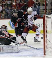 Columbus Blue Jacket's Derek MacKenzie (24), far right, scores against Carolina Hurricanes goalie Anton Khudobin (31) as Hurricanes' Justin Faulk (27) and Blue Jackets' Corey Tropp (26) look on during the first period of an NHL hockey game in Raleigh, N.C., Monday, Jan. 27, 2014. (AP Photo/Gerry Broome)