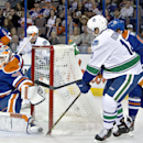 Vancouver Canucks' Nick Bonino (13) is stopped by Edmonton Oilers goalie Ben Scrivens (30) during first-period NHL hockey game action in Edmonton, Alberta, Friday, Oct. 17, 2014 The Associated Press